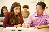foto of tutor  - Female High School Student With Teacher Studying At Desk - JPG