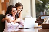 stock photo of 13 year old  - Mother And Teenage Daughter Looking At Laptop Together - JPG