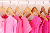 stock photo of wardrobe  - Female clothes on hangers in wardrobe - JPG