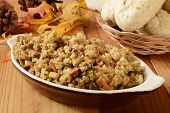 image of turkey dinner  - A bowl of turkey stuffing with dinner rolls on a holiday table - JPG