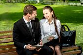 stock photo of work bench  - Young Business couple sitting on the bench and reading or working with tablets outdoors. ** Note: Soft Focus at 100%, best at smaller sizes - JPG