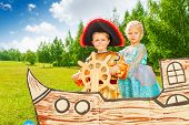 stock photo of pirate girl  - Boy as pirate holds helm and princess girl stand together on ship made of cardboard - JPG