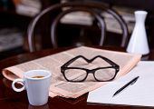 pic of newspaper  - Newspapers and coffee cup reading glasses pen and striped paper.