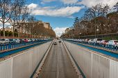 stock photo of tree lined street  - The prospect of the street with a descent into the tunnel in Madrid. The prospect of fences, cars, trees. Converging lines.