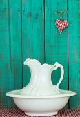 stock photo of pitcher  - Antique white water pitcher and basin on red gingham tablecloth by weathered teal blue wood wall with red checkered heart - JPG