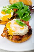 image of benediction  - Eggs benedict with bacon and spinach on white plate