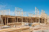 foto of framing a building  - New residential construction home framing against a blue sky - JPG