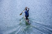 foto of canoe boat man  - Man in a canoe rowing on the tranquil lake - JPG