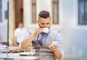 picture of lunch  - Modern hipster businessman drinking espresso coffee in the city cafe during lunch time and using mobile phone - JPG
