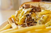 pic of cheesesteak  - A messy Philly Cheesesteak with onions and peppers with fries on the side - JPG
