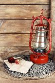 picture of kerosene lamp  - Kerosene lamp with dried rose and letter on wicker mat and wooden planks background - JPG