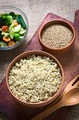 picture of quinoa  - Overhead shot of cooked white quinoa seeds in bowl with sesame and fried vegetables in the back photographed with natural light  - JPG