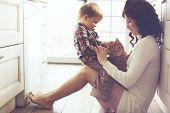 stock photo of petting  - Mother with her baby playing with pet on the floor at the kitchen at home - JPG