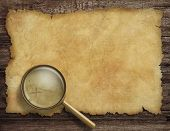 pic of treasure map  - Pirates old treasure map on wooden desk with magnifying glass - JPG