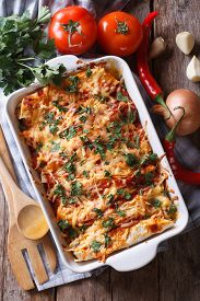 image of enchiladas  - Mexican enchilada in a baking dish with the ingredients on the table - JPG