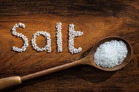 foto of crystal salt  - Sea salt on wooden spoon and the word salt written in grain - JPG
