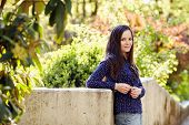 stock photo of stroll  - Young woman with long dark hair leaning on stone wall posing during stroll in park - JPG