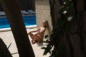 pic of sunbather  - Sexy girl takes a sunbath on swimming pool - JPG