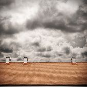 stock photo of roof tile  - stormy sky and tiled roof top background - JPG