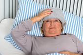 stock photo of forehead  - Sick Middle Aged Woman Lying Down on Bed with Towel on the Forehead While Looking up in Pensive Facial Expression - JPG
