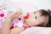 foto of sucking  - Beautiful little asian girl lying and suck up milk bottle in bed - JPG