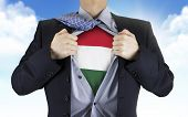 pic of hungarian  - businessman showing Hungarian flag underneath his shirt over blue sky - JPG