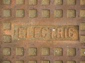 image of manhole  - A rusty manhole cover with the word Electric on it describing what utilities the cover gives access to - JPG
