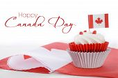 stock photo of happy day  - Happy Canada Day celebration cupcake with red and white Canadian maple leaf flag on white wood table and sample text - JPG