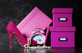 stock photo of girlie  - Ladies pretty pink female office desk with high heel shoe clock pen stationery filing boses pearls and diary organiser against a dramatic black background - JPG