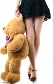 image of teddy-bear  - woman wearing skirt and high heels holding toy bear near her legs view of the back lower body part isolated on white background - JPG