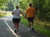 stock photo of fat woman  - overweight man and woman walking on trail in forest - JPG