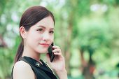 Beautiful Business Smart Look Asian Woman Calling With Smart Phone In The Park poster