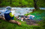 The Boy Sits On The Bank Of The River Near The Bonfire And Holds The Map, Near The Fire Is A Mug And poster