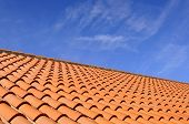 stock photo of roof tile  - Orange roof tiles made from a ceramic material and the sky above - JPG