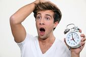 stock photo of tick tock  - Man in a panic after sleeping in - JPG