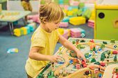 Постер, плакат: Children Play With Wooden Toy Build Toy Railroad At Home Or Daycare Toddler Boy Play With Crane T