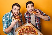 Portrait of a two hungry young men eating pizza isolated over yellow background poster