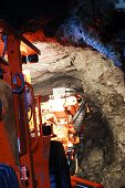 stock photo of gold mine  - heavy duty mine machine working in the shaft - JPG