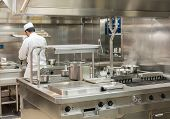 Chef Preparing Food In Commercial Stainless Steel Kitchen In Restaurant poster