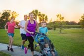 Beautiful, fit young family  jogging together outdoors along a paved sidewalk in a park pushing a st poster