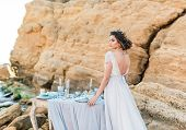 Beautiful Brunette Bride In Light Chiffon Wedding Dress Embroidered With Beads Posing Near The Sea.  poster