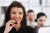 Three Call Centre Service Operators At Work. Portrait Of Smiling Pretty Brunette Woman At Workplace  poster