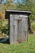 stock photo of outhouses  - an old outhouse with rusty hinges in a rural setting - JPG