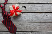 Happy Fathers Day Card With Copy Space, Present And Red And Black Striped Necktie On Rustic Wood Bac poster