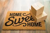 Home Sweet Home Welcome Mat On Wood Floor With Shipment of Boxes. poster