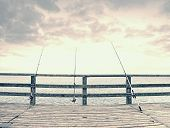 Fishing On Sea Bridge. Fishers Rods Against The Wooden Handrail Of The Beach Mole. Overcast Day, Wit poster