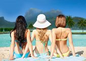 summer holidays, vacation, travel and people concept - group of women in swimwear sunbathing over bo poster