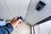 Garage Door Pvc. Hand Use Remote Controller For Closing And Opening Garage Door poster