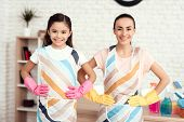 A Woman And A Girl Are Posing With Money For Cleaning The Apartment. They Are At Home. Behind Them I poster