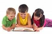 stock photo of reading book  - Group of children reading book together in studio - JPG